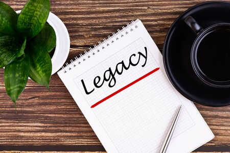 Legacy text, inscription, phrase is written in a notebook that lies on a wooden table and a pen. Business concept.