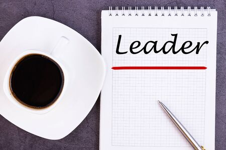 LEADER is written in a notebook lying on a grey table with a pen and a cup o coffee. Imagens