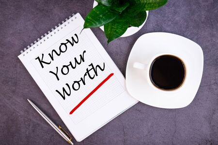 Know Your Worth word concept written in a notebook with pen and a cup of coffee, top view.