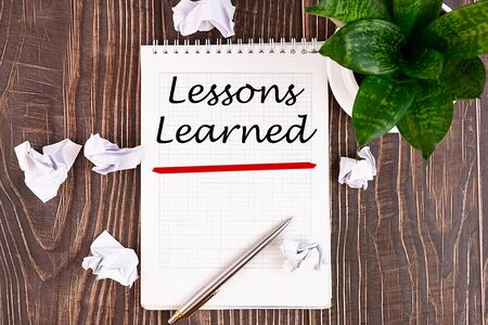 Lessons learned text concept written in a notebook with pen, top view.