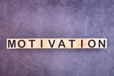 Word MOTIVATION made with wood building blocks on a gray background