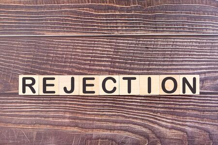 The word REJECTION, written with wooden cubes on a wooden background.