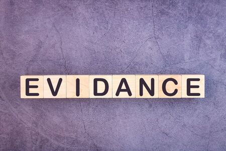 Evidence word written on a wooden blocks on a grey table, concept.