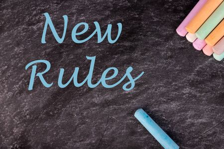 Piece of color chalk and text NEW RULES on blackboard, top view