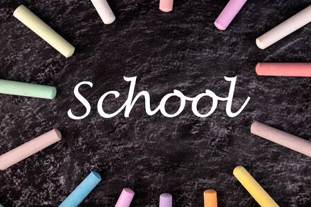 Text SCHOOL written with chalk on chalkboard, and some chalk sticks of different colors