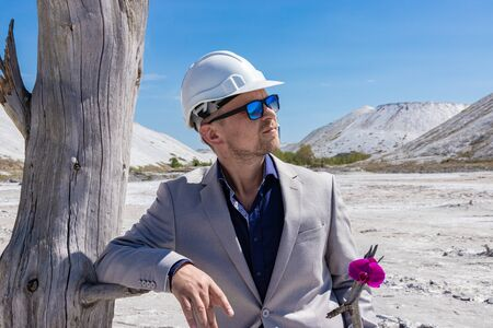 Ecology concept, businessman preserves orchid flower on a background of environmental disaster. Standard-Bild - 147411547