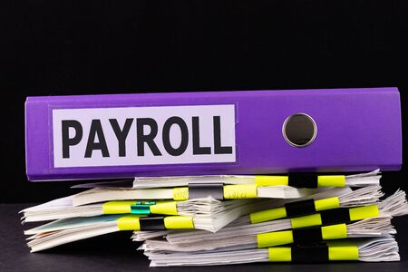 Text, word Payroll is written on a folder lying on documents on an office desk.