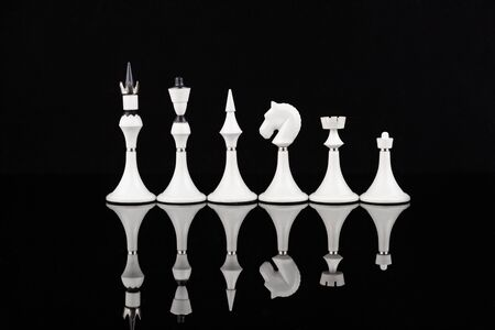 White chess pieces on a reflective surface. Business concept. Game, strategy, wisdom, determination. Фото со стока