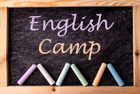 Pieces of color chalk and words ENGLISH CAMP on blackboard, flat lay Imagens