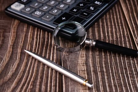 Pen, magnifying glass and part of a calculator on a wooden table. Financial concept. Фото со стока