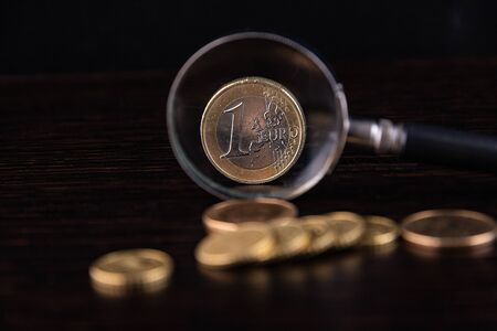 Magnifier and EURO coin on a black background