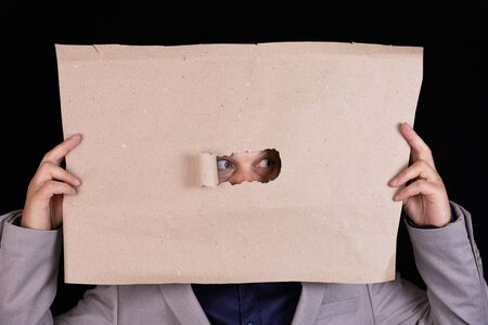 The business man is holding a sheet of paper with an opening for his eyes. Personalizes Censorship. Business concept Stockfoto