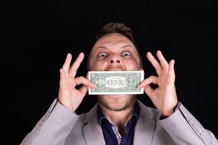 man businessman in a suit with his mouth closed and a dollar bill, silence for money. The concept of corruption and bribery. Business concept. Foto de archivo