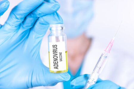 Text ADENOVIRUS VACCINE of is written on a bottle with the background of a doctor with a syringe in a medical glove and mask. Medical concept.