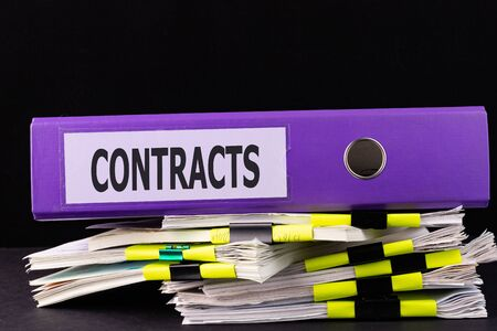 Text CONTRACTS is written on a folder lying on a stack of papers on a table. Business concept Zdjęcie Seryjne
