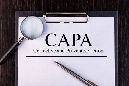 Text CAPA. Concept image of Business Acronym CAPA Corrective and Preventive action. is written on a notebook with a pen and a magnifying glass lying on the table. Business concept. Stok Fotoğraf