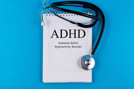 Notebook with text ADHD - Attention Deficit Hyperactivity Disorder, on a blue table with a stethoscope, medical concept.