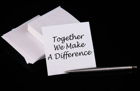 Conceptual hand writing Together we make the difference message on a white sticker with pen on a black table.