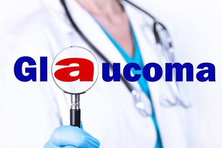 A doctor in medical clothes on a light background looks through a magnifying glass at the text Glaucoma. Medical concept.
