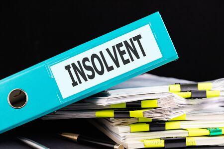 Text INSOLVENT is written on a folder lying on a stack of papers with a pen on the table. Business concept