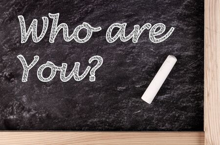 Who are you? text on blackboard with a piece of chalk.