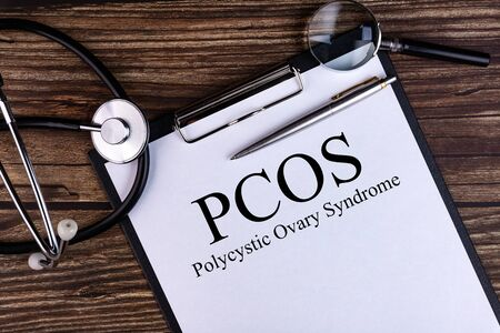 PCOS text is written on a tablet lying on a dark table with a stethoscope and a magnifying glass. Medical concept.
