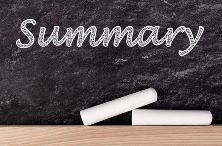 Summary text on blackboard with two pieces of chalk.