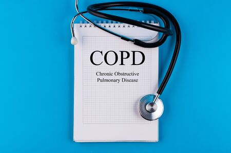 COPD text written in a notebook lying on a desk and a stethoscope. Medical concept.