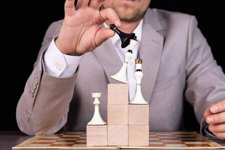 A businessman is building a pyramid of chess pieces and wooden blocks. The concept of construction, growth, development, success.