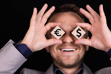 A businessman expresses emotions with his hands and face with wooden blocks and signs of EURO and dollar USA. Business concept for profit, income, win. Information. Symbol.