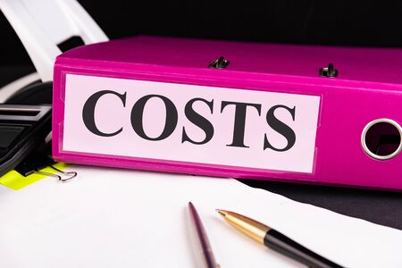 Text COSTS is written on a folder lying on a stack of papers with a pen on the table. Business concept.