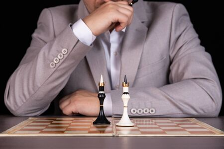 A man, a businessman sits at a chessboard. On the board is black and white king. Management concept, racial discrimination.