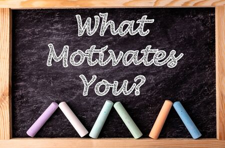 Chalkboard and color chalks with text What motivates you