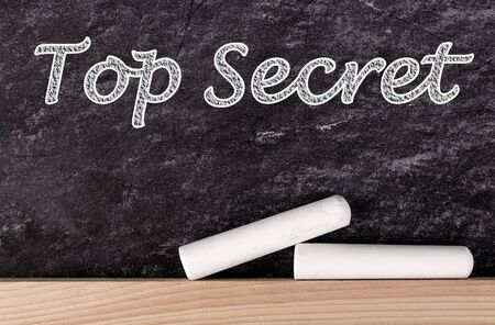 Top secret text on blackboard with two pieces of chalk.