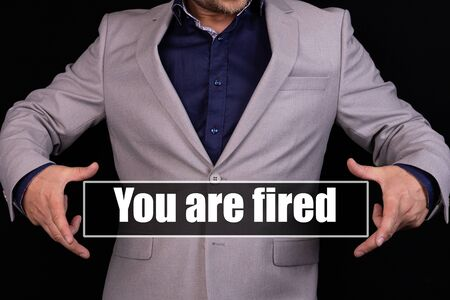 Concept You are Fired. Man holding an icon with a message text written on it.