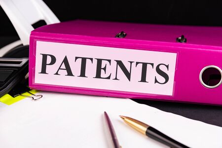 Text PATENTS is written on a folder lying on a stack of papers with a pen on the table. Business concept. Foto de archivo