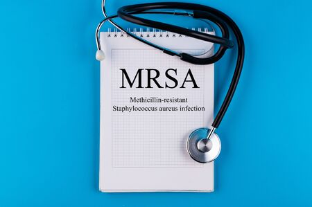 Page with MRSA Methicillin-resistant Staphylococcus aureus infection on the table with stethoscope, medical concept