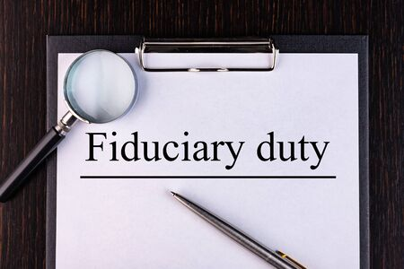 Text FIDUCIARY DUTY is written on a notebook with a pen and a magnifying glass lying on the table. Business concept. Stock fotó