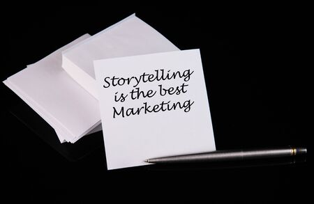 Conceptual hand writing Storytelling is the best Marketing message on a white sticker with pen on a black table. Standard-Bild