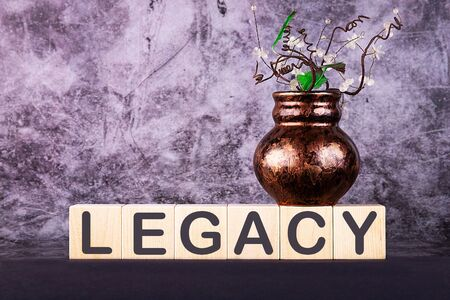 Word LEGACY made with wood building blocks on a gray back ground