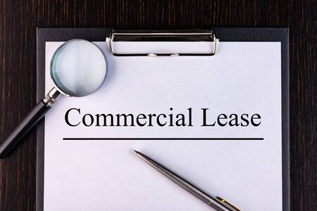 Text COMMERCIAL LEASE is written on a notebook with a pen and a magnifying glass lying on the table. Business concept. Reklamní fotografie
