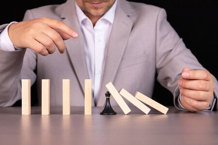 A chess pawn stops a wooden domino from falling - this is the effect of a continuous fall or risk, strategy and concept of successful intervention for a business. Foto de archivo
