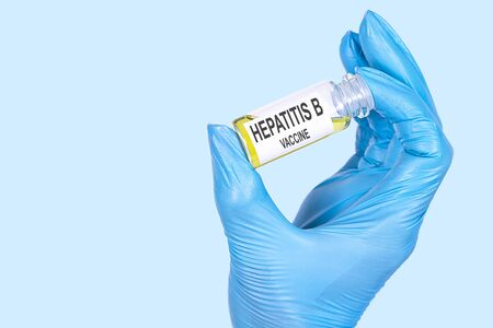 HEPATITIS B VACCINE text is written on a vial whose ampoule is held by a hand in a medical disposable glove. Medical concept.