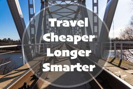 Travel Cheaper Longer Smarter - inspirational quote on the background of the railway bridge Standard-Bild