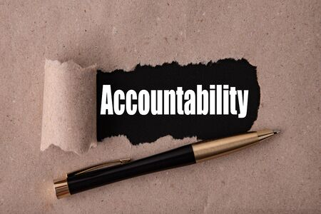 The word Accountability is written under tear paper on a black background with a pen. High quality photo