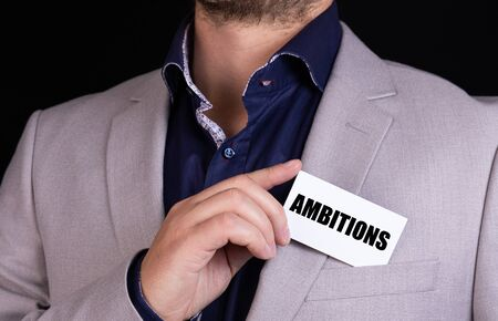 AMBITIONS text on the blackboard is written on the card that the businessman put in his jacket pocket. Business concept