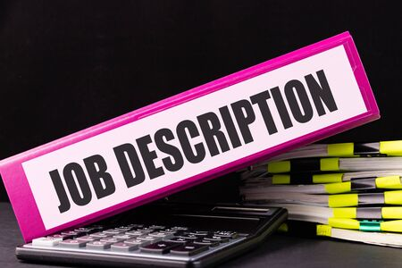 JOB DESCRIPTION text is written on a folder lying on a stack of papers on an office desk. Business concept.