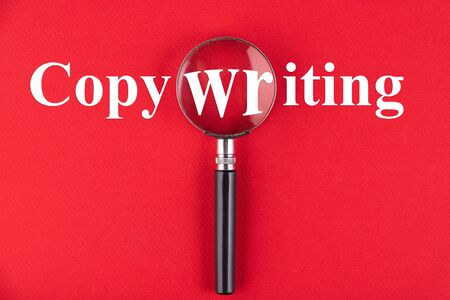 COPYWRITING text written through a magnifying glass on a red background. Business education concept.