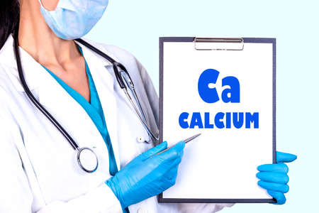 CALCIUM Ca text is written on a tablet which the doctor holds in a medical gown and gloves. Medical concept. Stok Fotoğraf
