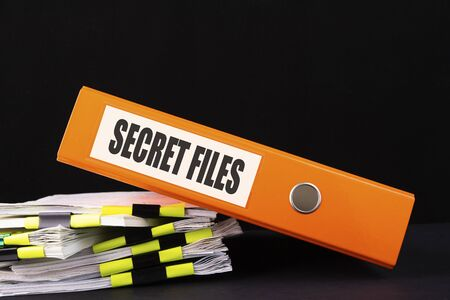Secret files inscription on the Office folder on a dark desktop with documents.